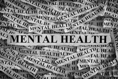 psychosocial: Mental health. Torn pieces of paper with the words Mental health. Concept Image. Black and White. Closeup.