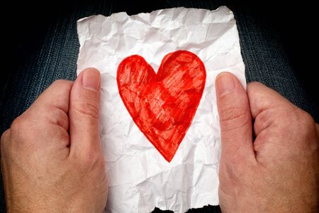 personas tristes: Young man holding crumpled piece of paper with red heart at night.