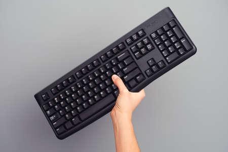 cross process: Person holds black wireless keyboard in her hand. Cross process.
