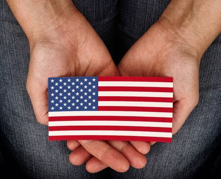 patriotism: Woman holding American flag on her palms. Patriotism and freedom concept. Stock Photo