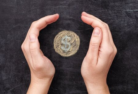 Hands protecting drawn dollar coin on black chalkboard background. Close up.