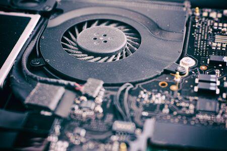 Laptop ventilator met stof in het en het moederbord. De nadruk ligt op ventilator. Detailopname.