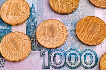 rubles: Ruble coins on one thousand rubles banknote. Close up.