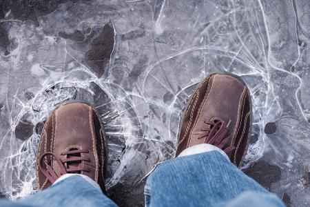 男凍った水たまり薄氷を踏む。