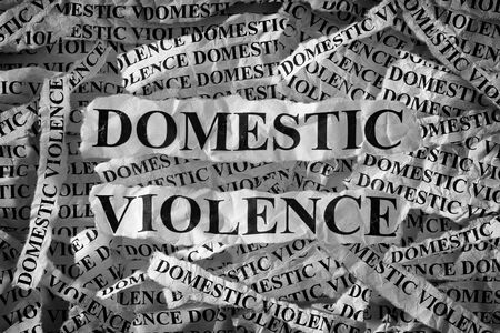 Domestic violence. Torn pieces of paper with the words Domestic violence. Concept Image. Black and White. Closeup. Banco de Imagens
