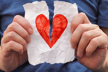 love shape: Young man ripping red heart on a piece of paper. Close up.