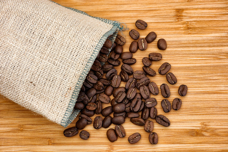 Coffee beans spilling out of burlap bag. Close up.