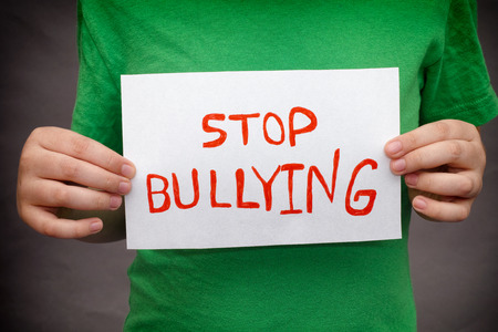torment: A young boy holds Stop bullying sign.