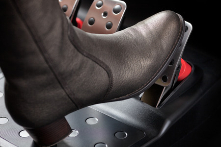 Woman pressing the gas pedal with her foot. Close up.