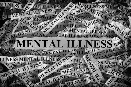 psychosocial: Mental illness. Torn pieces of paper with the words Mental illness. Concept Image. Black and White. Closeup.