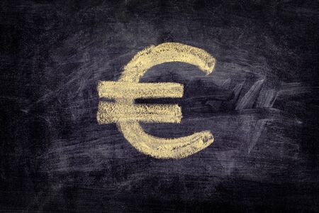 euro sign: Drawn euro sign on black chalkboard background. Close up.