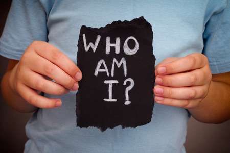 Child holds piece of black paper with question Who am I?. Close up.
