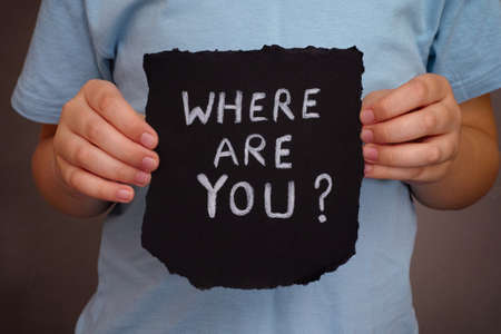 where: Child holds piece of black paper with question Where are you?. Close up.