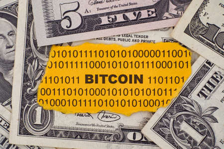 crypto: Piece of paper with the word Bitcoin on dollar bills. Close up.