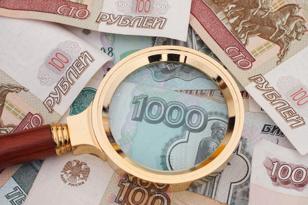 money crisis: Magnifying glass and russian money. Crisis concept. Stock Photo