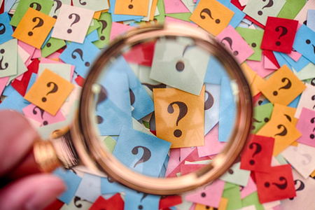Pile of colorful paper notes with question marks and magnifying glass. Closeup.