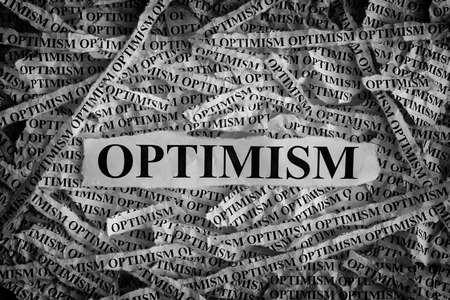 idealism: Optimism. Torn pieces of paper with the word Optimism. Concept Image. Black and White. Closeup.