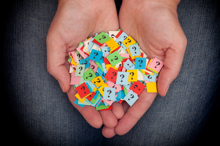 too: Too Many Questions. Pile of colorful paper notes with question marks in woman hands. Closeup. Stock Photo
