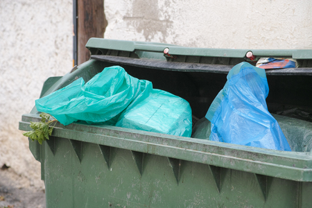 dumpster: Green trash dumpster full of garbage. Close up.