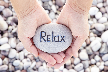 laze: Woman holding stone with the word Relax in her palms. Close up.