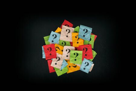 Too Many Questions. Pile of colorful paper notes with question marks on blackboard. Closeup. Stock Photo