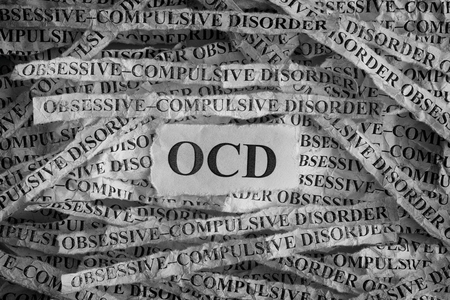 Obsessive compulsive disorder (OCD). Torn pieces of paper with the words Obsessive–compulsive disorder. Concept Image. Black and White. Closeup.