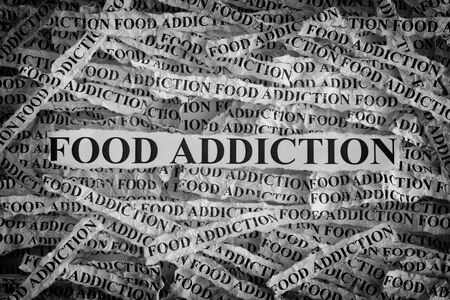 Food Addiction. Torn pieces of paper with the words Food Addiction. Concept Image. Black and White. Closeup. Standard-Bild