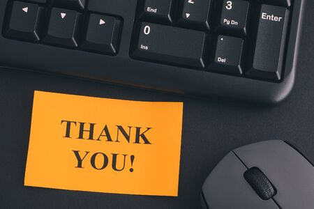 Thank You!. Paper note with writing Thank You! on a desk with black keyboard and grey wireless mouse. Close up.