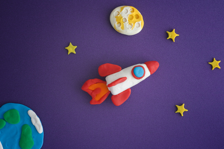Space Rocket Blasting Off For New Ideas. Earth, space rocket, Moon and stars are made out of play clay (plasticine). Stock Photo