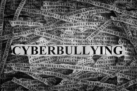Cyberbullying. Torn pieces of paper with word Cyberbullying. Concept Image. Black and White. Closeup. Stock Photo