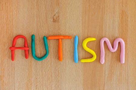 Autism. Autism spectrum disorder. Autism word made out of playdough. Wooden background. Close up. Stock Photo