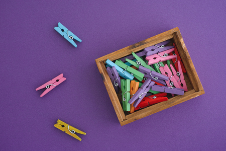 Colourful clothespins in a wooden box on purple background. Close up.