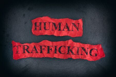 Crumpled pieces of paper with the words Human Trafficking. Close up.