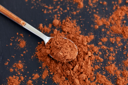 Spoon filled with organic cocoa powder. Top view. Natural lighting. Reklamní fotografie - 116436368