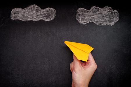 Mains tenant un avion en papier jaune sous les nuages. Fermer. Banque d'images