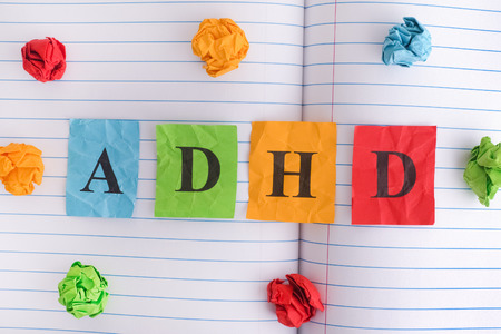 ADHD. Abbreviation ADHD on notebook sheet with some colorful crumpled paper balls around it. Close up. ADHD is Attention deficit hyperactivity disorder.