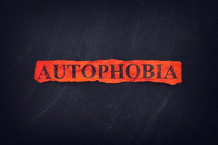 Word Autophobia on red torn piece of paper. Autophobia - fear of being alone.
