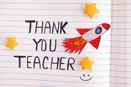 Thank You Teacher. Lined paper notepad with words Thank You Teacher and with Space Rocket Blasting Off  Through Yellow Origami Stars. Close up.