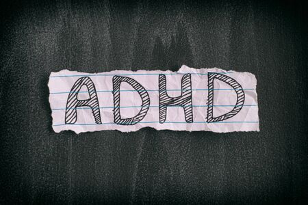 ADHD. Abbreviation ADHD on black background. Close up. ADHD is Attention deficit hyperactivity disorder. Stock Photo