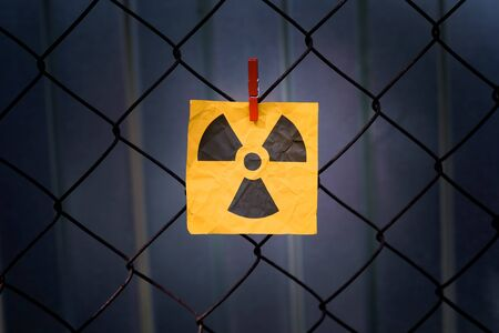 Radiation warning sign hanging on a metal mesh fence. Close up.