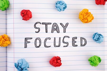 Stay Focused. Phrase Stay Focused on notebook sheet with some colorful crumpled paper balls around it. Close up.