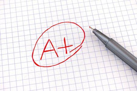 Ein Plus (A+) Note auf Notizbuchpapierblatt. Nahaufnahme. Standard-Bild