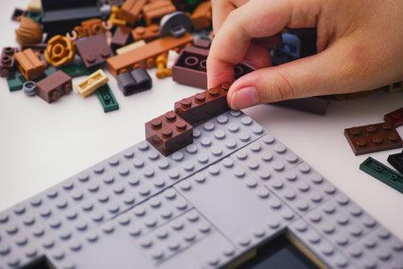 Tambov, Russian Federation - January 02, 2020 Child placing a Lego brick on to plate. Studio shot.