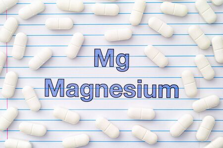 The word magnesium and magnesium tablets around it. Close up. Archivio Fotografico