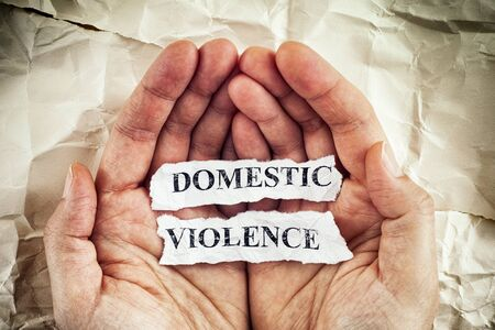 Domestic violence. Woman holding torn pieces of paper with the words Domestic Violence written on them in her palms. Concept Image. Closeup.
