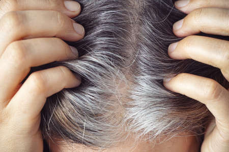 A woman showing her gray hair roots. Going gray concept. Close up.