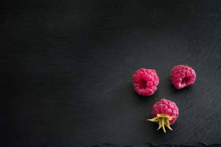 Organic raspberries on a black stone background. Low Key. Close up.