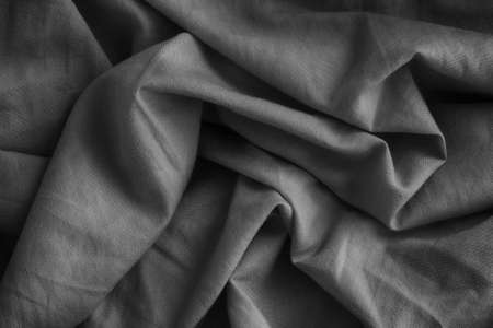 Wrinkled fabric texture background. Black and white. Low key. Close up.