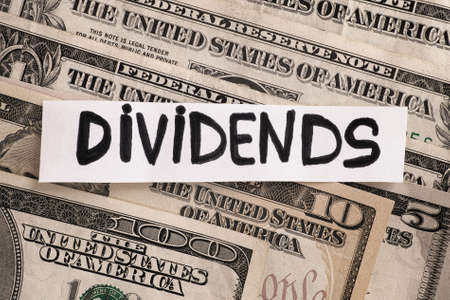 The word Dividends on dollar bills. Close up.