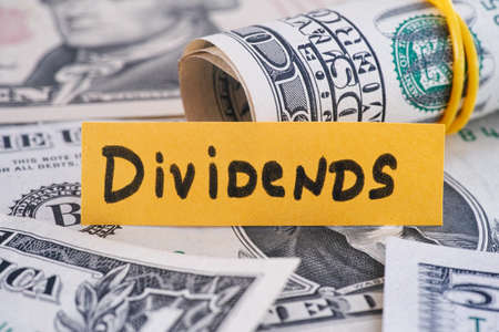 The word Dividends and dollar bills. Close up.